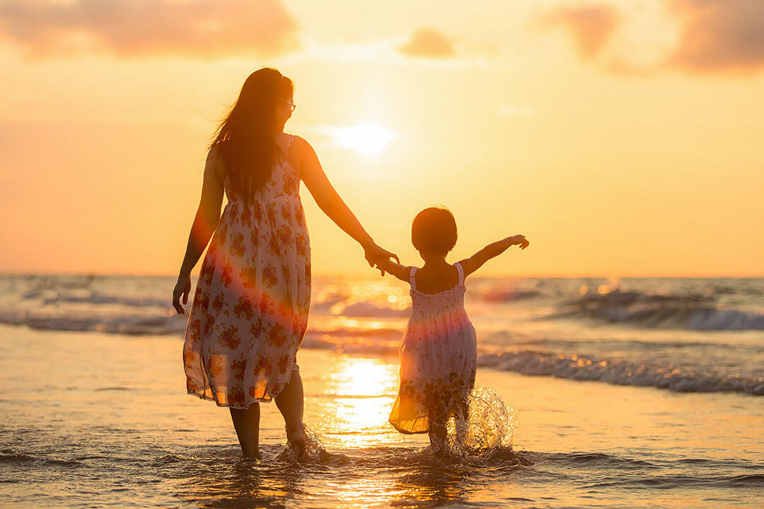 eco-friendly parenting on the beach with a sunset and golden water