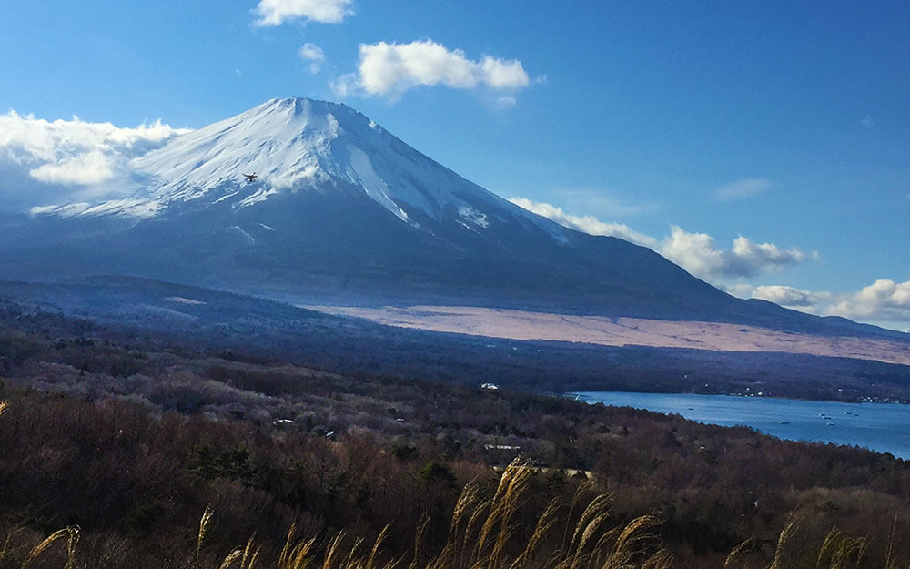 Japan snow mountain with blue clear sky and a lake on the right side showing the eco-friendly environment while traveling